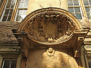 A large decorated shell-like stone canopy, with a shield in the centre and carved foliage around; a cherub's head underneath the hood