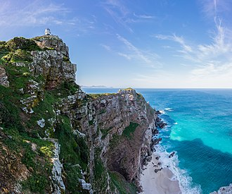 Cape Point - Looking from behind the old lighthouse (at top left) to the new lighthouse (a sunlit speck of white very near the point). The lighthouses are 700 metres apart, and the new lighthouse 162 metres lower in altitude so as to remain visible during low cloud.