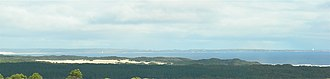 Ocean Beach (Tasmania) - Cape Sorell lighthouse on right, Ocean beach at left and behind sandhills in foreground