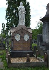 Een uitgebreid grafmonument van rood graniet, met twee witmarmeren tondi van Blondin en zijn vrouw, met daarboven een marmeren beeld van een vrouwelijke figuur gekleed in gewaden met een anker