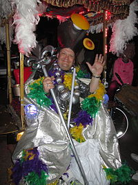 Andy Richter smiling and waving wearing an elaborate and colorful costume