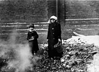 Child and adult collecting coal or coke.jpg