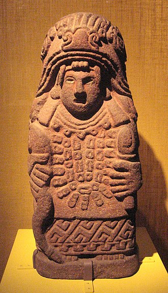 Cihuacōātl - Stone statue of Cihuacōātl, showing her framed by the mouth of a serpent, holding an ear of maize in her left hand.