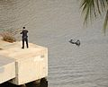 Cop checking out bag in the Ala Wai Canal (5361627543).jpg