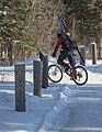 Cyclist wearing skis turns onto path (12711536603).jpg