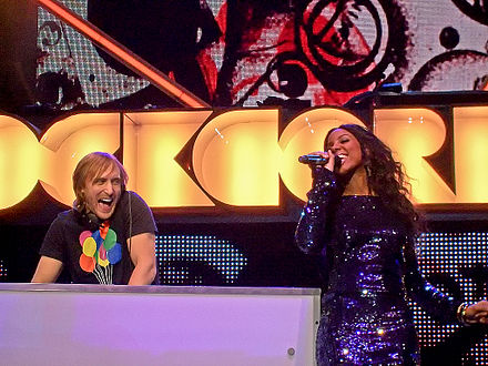 David Guetta and Rowland performing at the Orange Rockcorps in London in 2009. David Guetta and Kelly Rowland Live - Orange Rockcorps London 2009 reworked.jpg