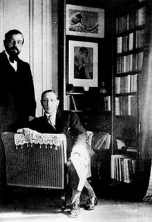 dos hombres blancos, uno barbudo, de mediana edad, de pie, el otro más joven, sentado, en una habitación llena de libros