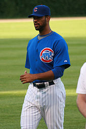 "A dark skinned man in white pinstriped pants, a blue baseball jersey, and a blue baseball cap. The jersey and cap each have a red ""C"" on them."
