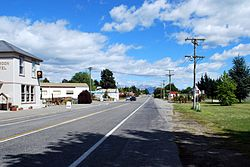 A straight road, divided by painted lines, passing through a town. On the left, the street is lined a pub and some widely separated shops. On the right, the road is lined by a grass verge with some small buildings in the middle distance. A black utility (car with a tray) is driving on the left away from the camera. A mountain range with a small covering of snow is in the background.