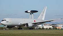 Side view of Japan military reconnaissance aircraft on airport runway, with dorsal mounted sensor pallet.