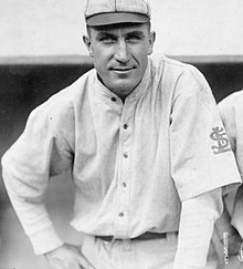 "A man in an old-style white baseball uniform with an interlocking ""StL"" on the left sleeve"
