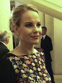 Woman with blond hair in three-quarter profile. Hair is held up in a ponytail, a pearl earring is visible.