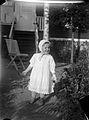 En liten flicka i vit sommarklänning och vit knytmössa på en trädgårdsgång - Nordiska Museet - NMA.0057544.jpg