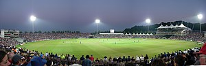 Panorama of a heavily populated cricket ground at night. A large stand is on the right-hand side of the pitch and the scene is illuminated by four floodlights.