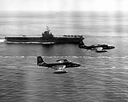 F2H-2 Banshees of VF-172 fly by USS Essex (CV-9) off Korea, circa 1951 (NH 97270).jpg