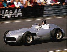 Photo couleur de Fangio, pilotant une Mercedes-Benz W196 grise en 1986