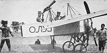 Two men seated in a World War I-era biplane, surrounded by technical personnel.