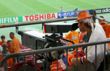 Photo de profil d'un cameraman en tribune filmant le terrain de football.