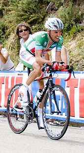 A cyclist in a green and white jersey with red trim, with a pained look on his face as he strains to climb a hill on his own. Spectators watch him from behind a barricade.