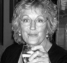 A middle-aged woman drinking a glass of wine.