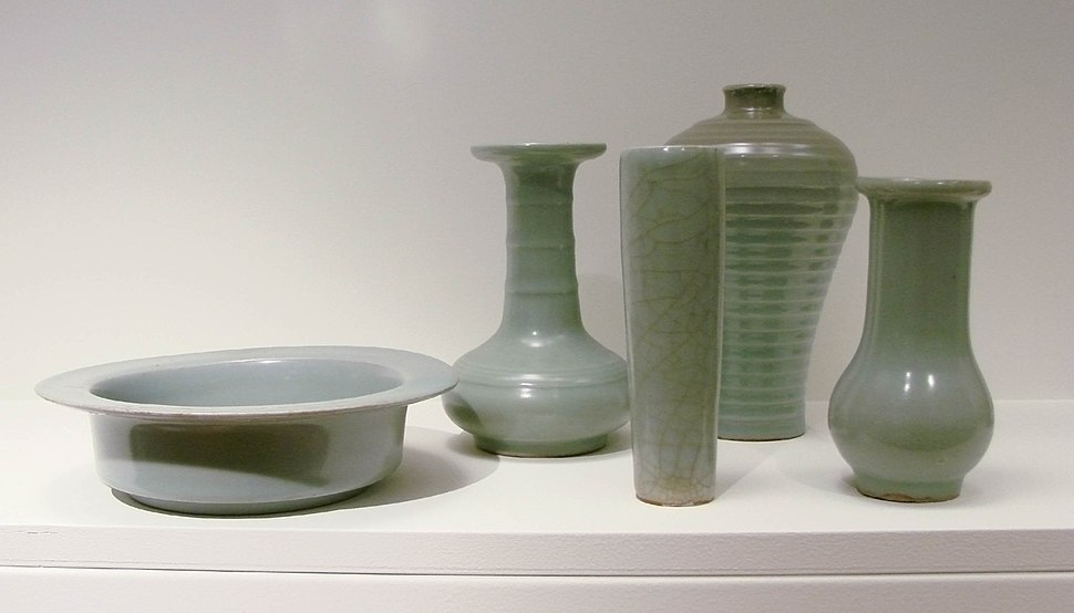 Five pieces of pale green pottery. From left to right, a cylindrical bowl with a large, flat rim, a vase with a long, thin stem and a short, almost spherical body, a tall, thin glass, a wider vase with no stem, and a small opening at the top, and a vase with a long, but wide stem and an almost spherical body.