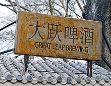 "A slightly rusted gray metallic sign with ""Great Leap Brewing"" written on it and four Chinese characters below"