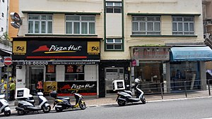 Pizza in China - A Pizza Hut restaurant in Happy Valley, Hong Kong-some of the scooters in front of the store are used for pizza delivery.
