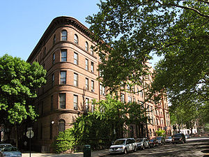 Brick townhouse along a street, which is lined with trees.