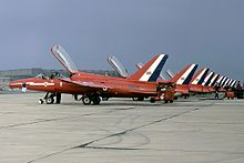A squadron of one-man jet aircraft, with their canopies open, lined up at a military airbase.