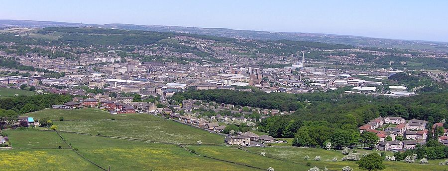 Closest wooded uplands in the inner part of the town's green belt, the town centre and the crest of the Pennines to the west: semi-panorama from Castle Hill. Three converted neoclassical mill sheds are in the foreground. Huddersfield1000px(RLH).jpg