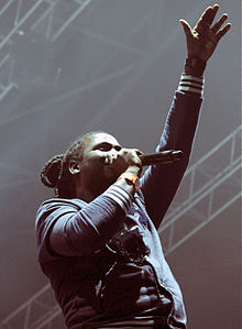 Man wearing dreadlocks in a bun singing into microphone, arm outstretched