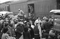 Los Angeles, California. Japanese Americans going to Manzanar gather around a baggage car at the old Santa Fe Station. (April 1942)
