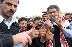 Iraqi parliamentary election, January 2005 - Iraqi police officers hold up their index fingers marked with purple indelible ink, a security measure to prevent double voting.