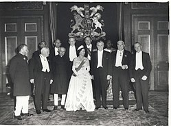 A formal group of Elizabeth in tiara and evening dress with eleven prime ministers in evening dress or national costume.
