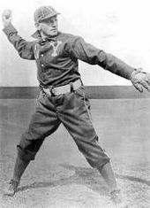 A black-and-white picture of a man in a blue baseball uniform and a white hat winds up to throw a baseball