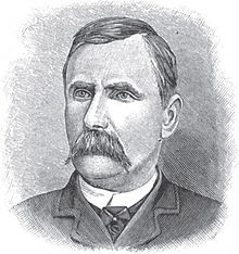 A man with dark hair and a dark mustache wearing a white shirt, black tie, and black jacket