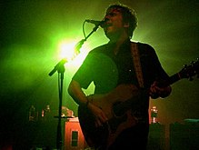Guitarist singing onstage, backlit by a green light