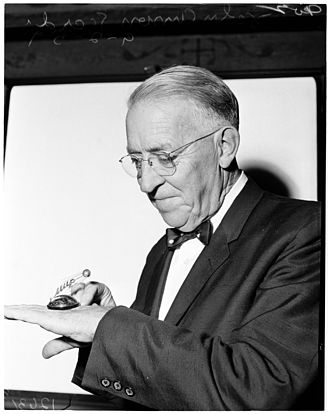 John Anson Ford - 1959 photo with miniature gold Sputnik given to him by Russian Premier on his recent trip to that country.