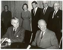 Diefenbaker and a Dwight Eisenhower sit at a table. Two women and three men stand behind them.