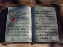 "A sculpture in the form of an open book. The text of the poem ""In Flanders Fields"" is written within and a small red poppy lays on top."