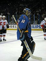 An ice hockey goaltender skates towards the right of the picture. He wears a blue jersey and blue helmet, with black leg pads and blocker