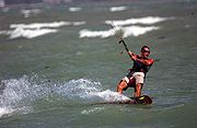 Kitesurfers use power kites hooked into harnesses to glide through water and air
