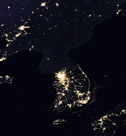 Satellite image of the Korean Peninsula at night, showing North Korea in almost complete darkness, with one small bright spot, the capital Pyongyang Korean Peninsula at night from space.jpg