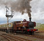 A pannier tank locomotive is passing a semaphore signal, leading a train which includes one visible passenger carriage. The pannier tanker is maroon, apart from the black chimney, brass safety valve cover,  red buffer beam, and grey coupling rods. The tank, cab, splashers and toolbox are all lined in yellow. London Transport is written on the side of the tank, and L.94 on the side of the cab, again both in yellow. A plume of brown smoke comes from the chimney, and there is as whisp of steam from under the pannier tank. The passenger carriage is cream and brown with a grey roof.