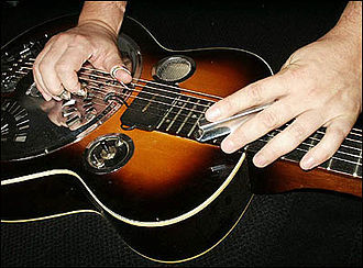 Slide guitar - Wooden resonator guitar played with a steel, angled to form a chord unavailable from straight open tuning.