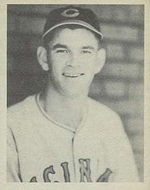 "A man smiles for the camera while wearing a dark cap with a ""C"" on the center and a white baseball jersey."