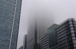 A large building heads up into the sky. Only a portion of the building is visible, as the top is engulfed in a thick fog.