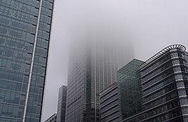 В небо взмывает большое здание.  Видна только часть здания, так как вершина окутана густым туманом.