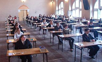 Standardized test - Young adults in Poland sit for their Matura exams.  The Matura is standardized so that universities can easily compare results from students across the entire country.
