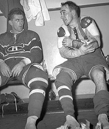 Richard, in full uniform except for his skates, sits on a locker room bench and stares at teammate Toe Blake beside him.
